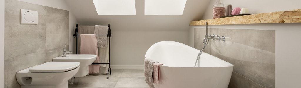 Gefliestes Badezimmer im Dachgeschoss mit freistehenden Badewanne und einer Toilette