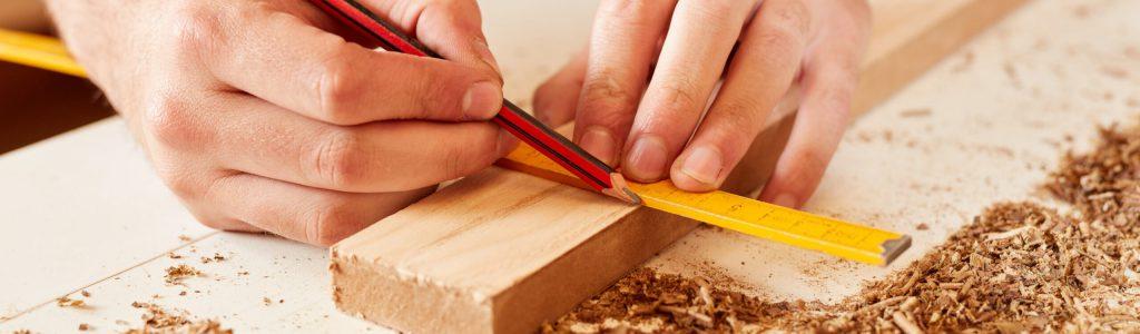 Handwerker mit Zollstock und Bleistift beim Holz Abmessen in der Werkstatt